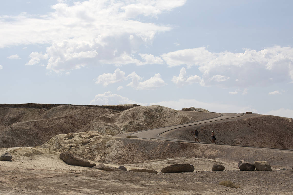 Tourists walk the road up to Zabriskie Point on a 127-degree day on Monday, Aug. 17, 2020 in De ...