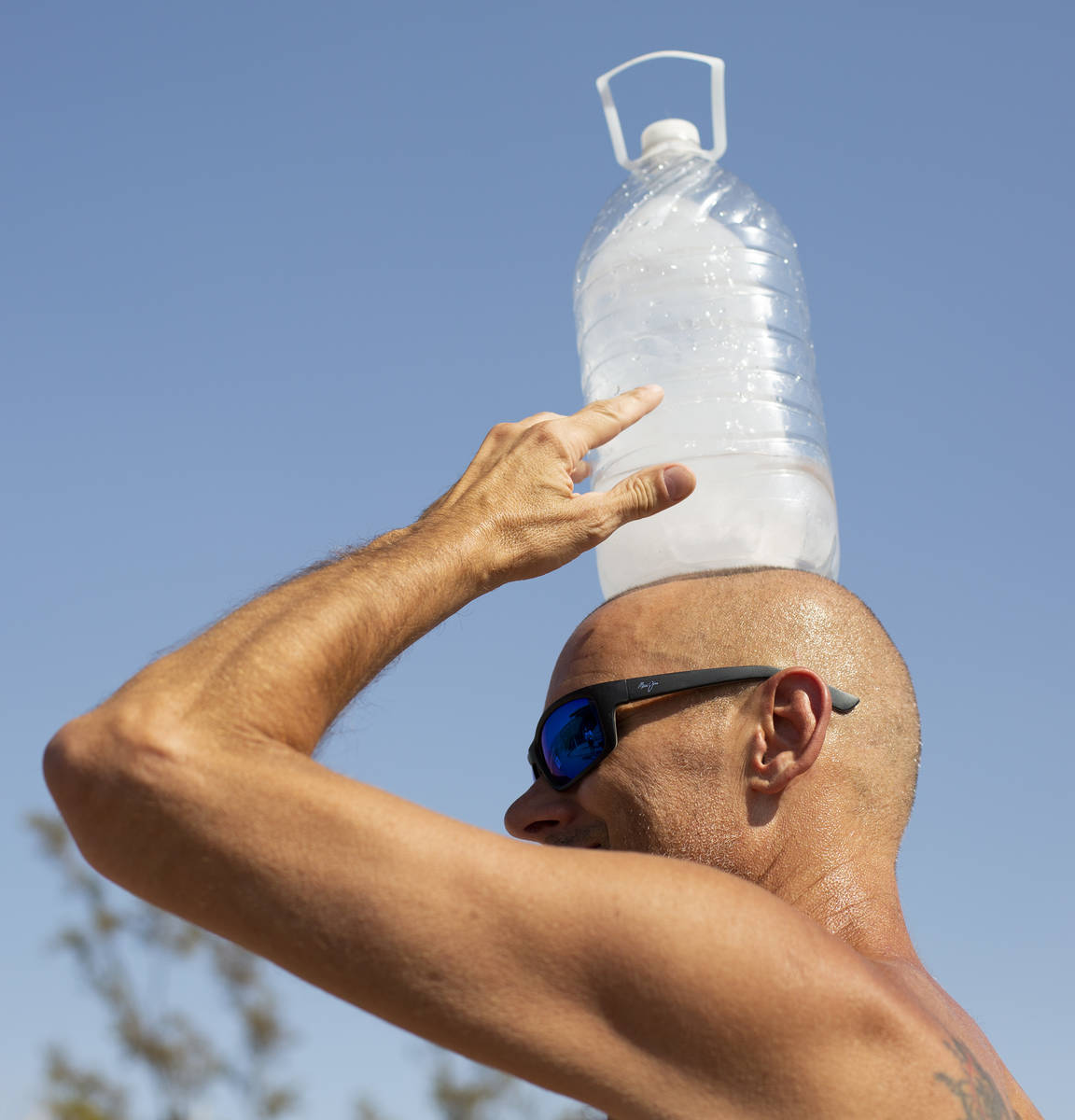 Steve Krofchik of Las Vegas holds ice on his head outside Furnace Creek Visitor Center at Death ...