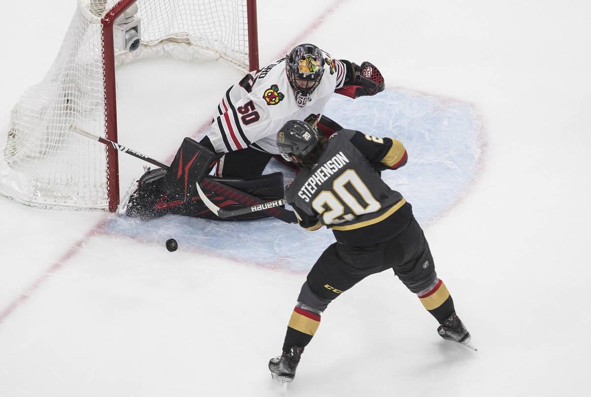 Vegas Golden Knights' Chandler Stephenson (20) is stopped by Chicago Blackhawks goalie Corey Cr ...