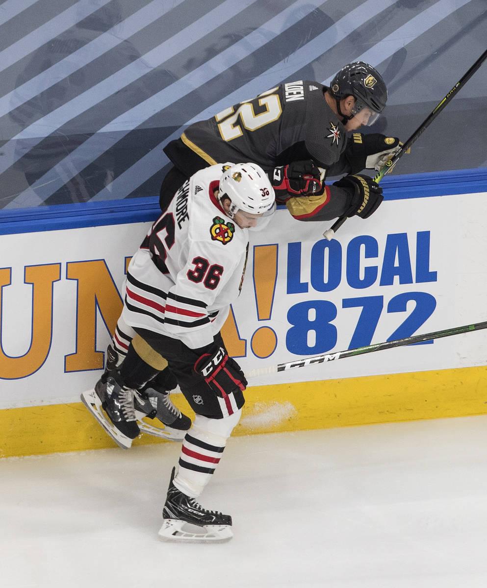 Vegas Golden Knights' Nick Holden (22) is checked by Chicago Blackhawks' Matthew Highmore (36) ...