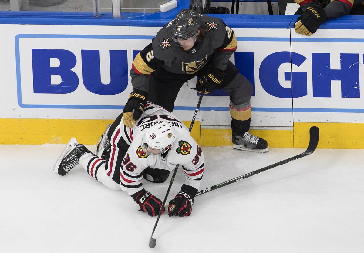 Vegas Golden Knights' Zach Whitecloud (2) checks Chicago Blackhawks' Matthew Highmore (36) duri ...