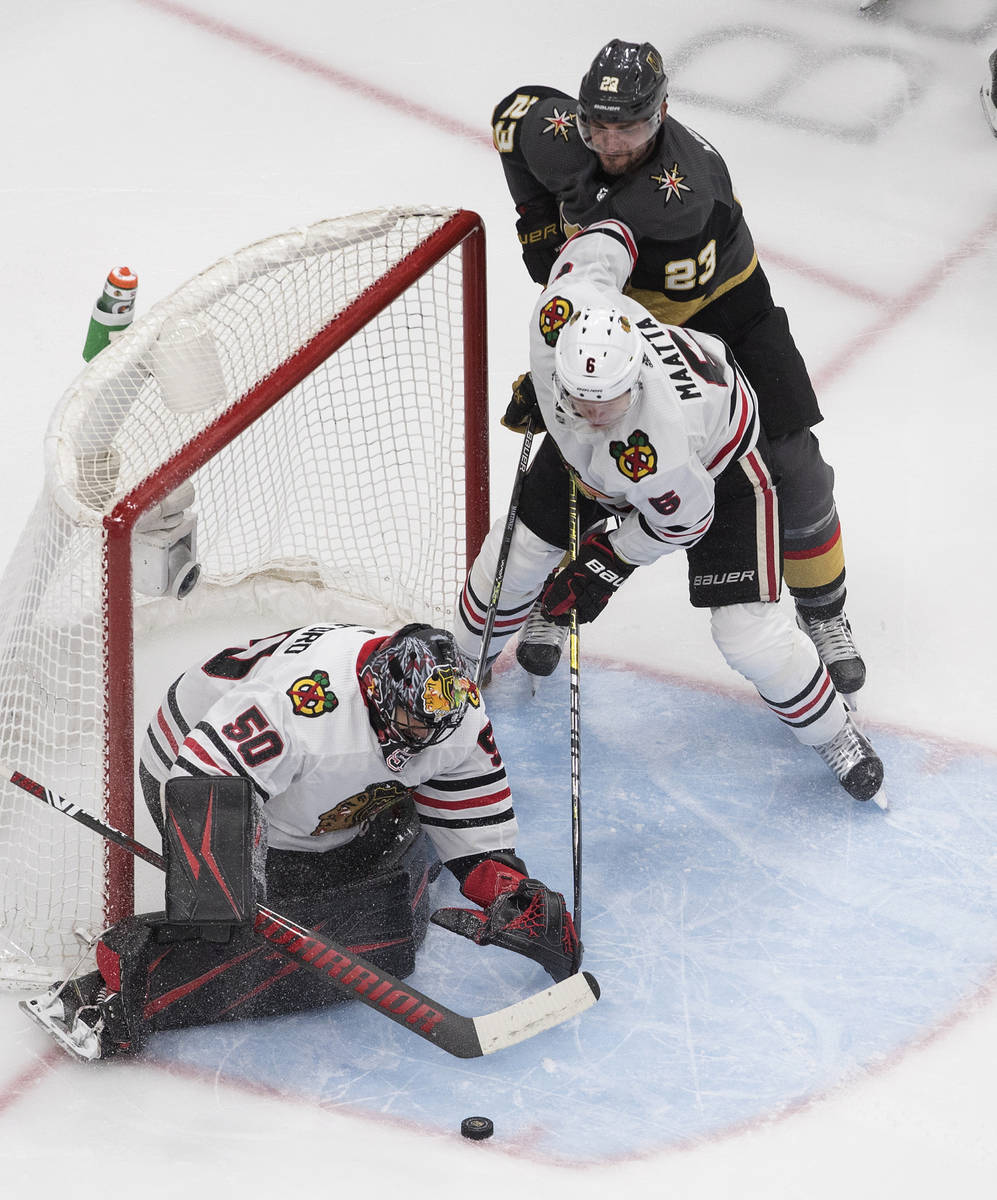 Vegas Golden Knights' Alec Martinez (23) and Chicago Blackhawks' Olli Maatta (6) look for a reb ...