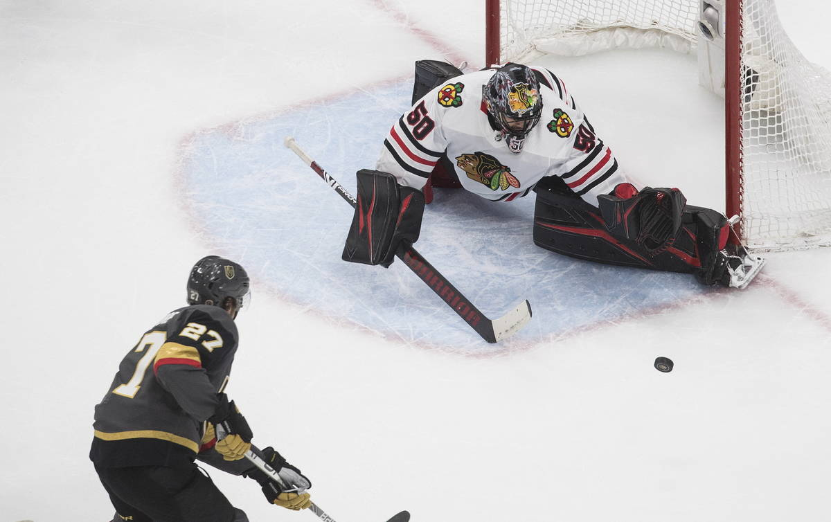 Vegas Golden Knights' Shea Theodore (27) is stopped by Chicago Blackhawks goalie Corey Crawford ...