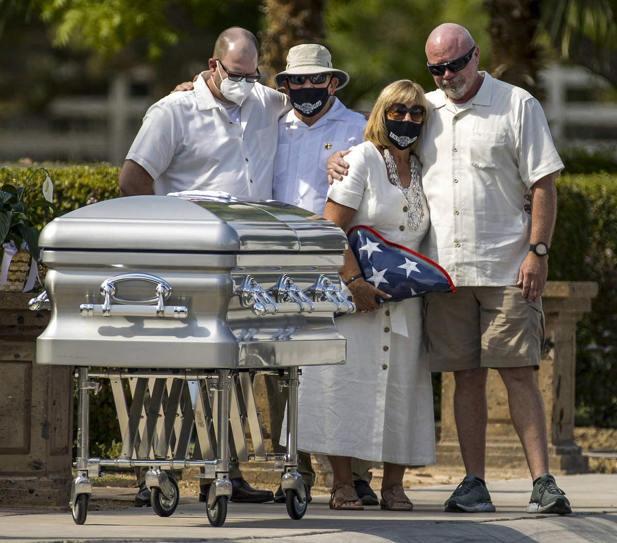 Mourners gather about the casket during a burial service for Metro Lt. Erik Lloyd at the Palm N ...
