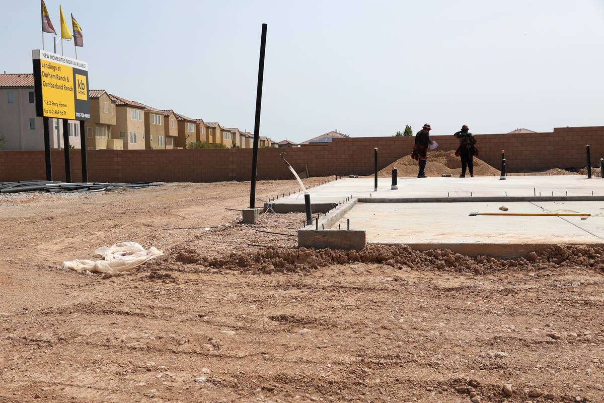Workers stand on the slab foundation of a future home near S Fort Apache Road and W Gomer Road ...