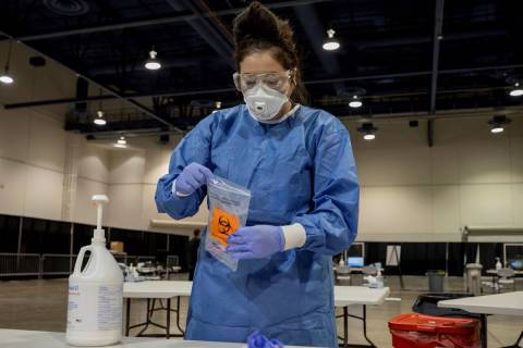 UMC respiratory therapist Diana Vega seals a COVID-19 test in a biohazard bag during a preview ...