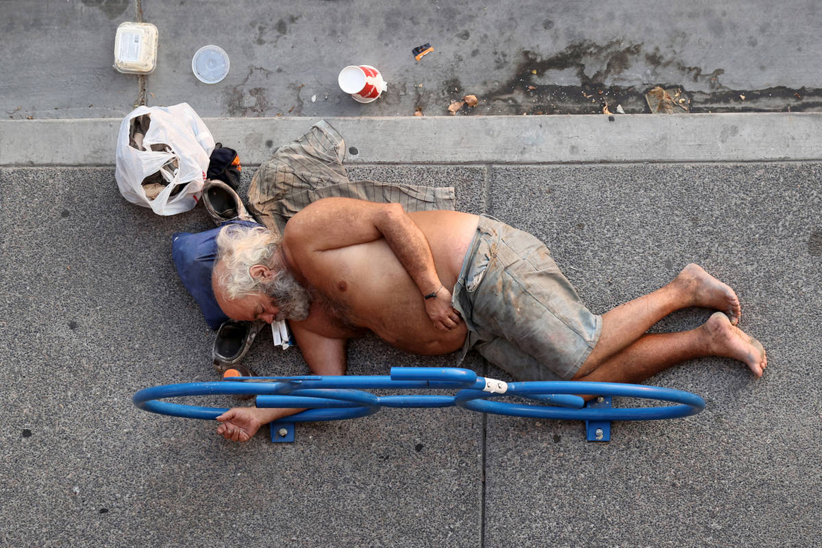 A person rests in the shade Ogden Avenue near Las Vegas Boulevard Tuesday, Aug. 18, 2020. (K.M. ...