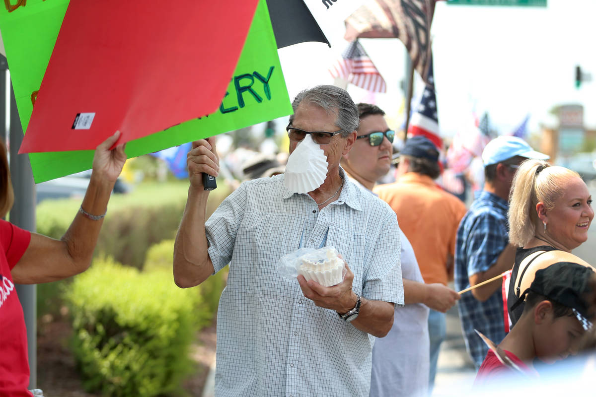 Bill Henggler of Henderson, 72, wears a coffee filter on his face while attending a No Mask Nev ...