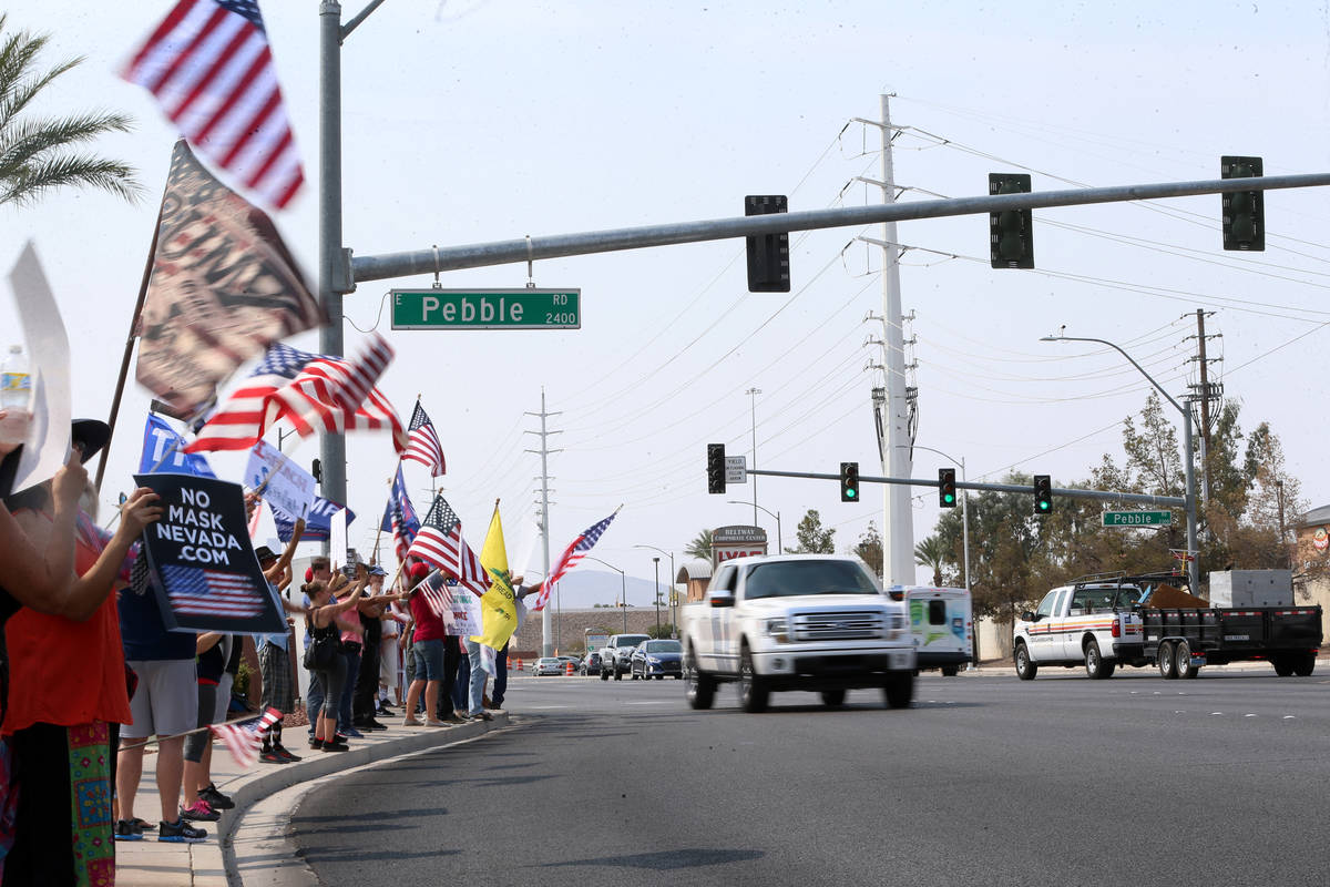 People attend a No Mask Nevada PAC rally at the intersection of Eastern Avenue and Pebble Road ...