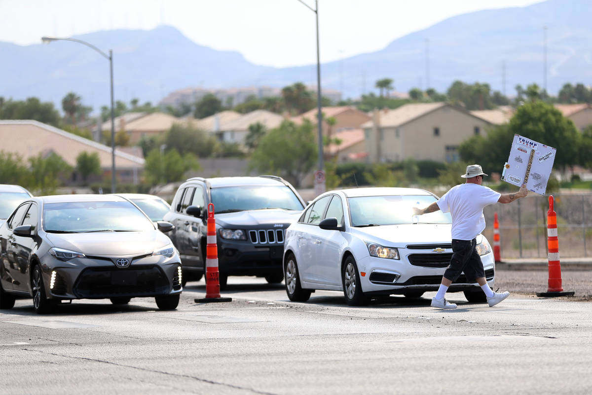 A protester walks on the crosswalk holding up his sign during a No Mask Nevada PAC rally at the ...