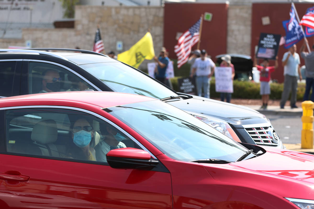 People in their cars look out to a No Mask Nevada PAC rally at the intersection of Eastern Aven ...