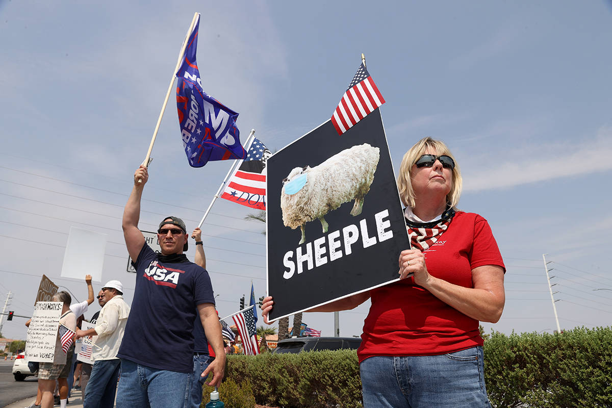 Colene Stevens of Henderson, right, participates during a No Mask Nevada PAC rally at the inter ...