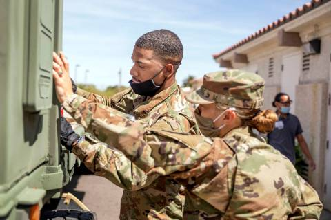 Nevada National Guard specialist Donshay Watkins, left, and Sgt. Vanessa Gonzales unload person ...