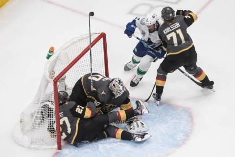 Vegas Golden Knights' Shea Theodore (27) crashes against goalie Robin Lehner (90) as Vancouver ...