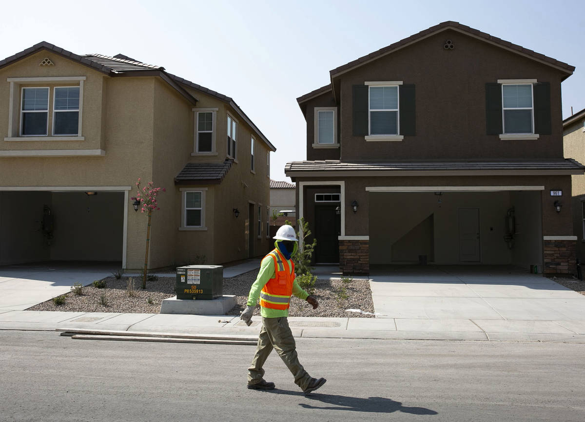 A construction worker walks past single family homes at a single-family-housing rental project ...