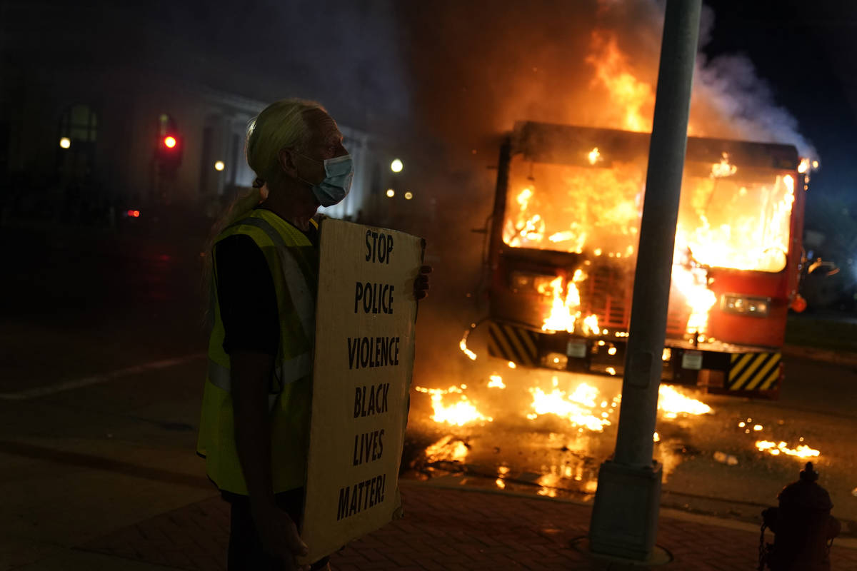 A protester stands near a burning garbage truck outside the Kenosha County Courthouse, late Mon ...
