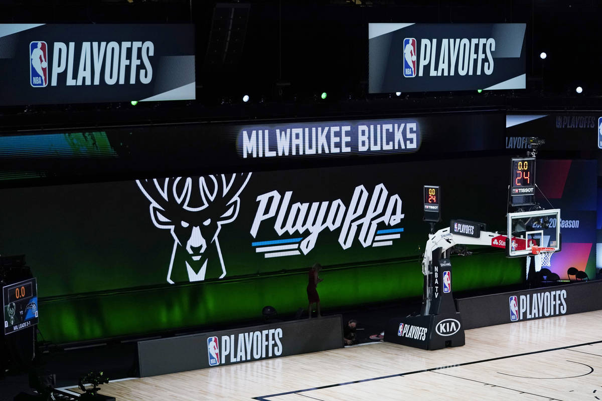 Milwaukee Bucks signage is displayed on screens beside an empty court before the scheduled star ...