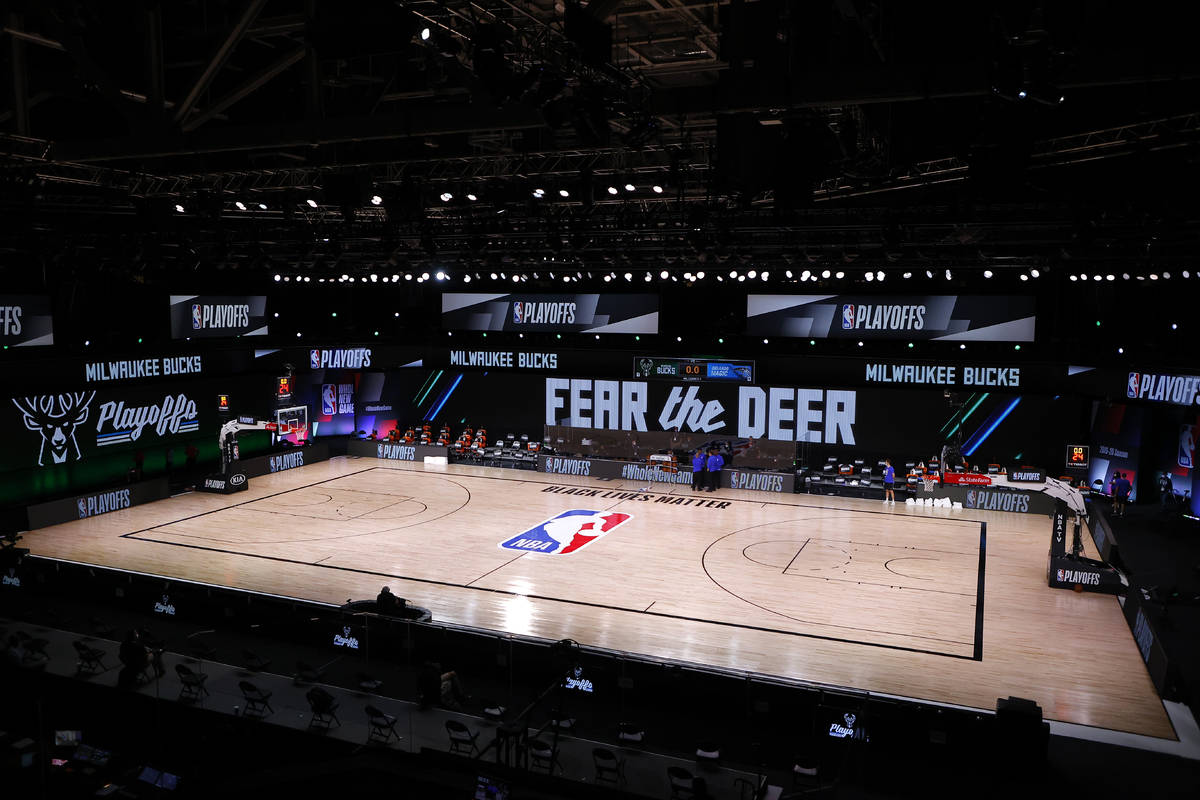 Referees huddle on an empty court at game time of a scheduled game between the Milwaukee Bucks ...