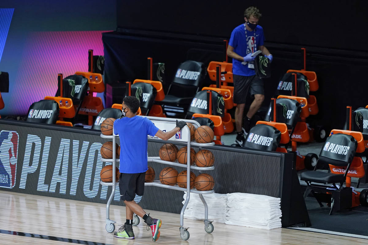 Workers clear items from the Milwaukee Bucks bench after the scheduled start time of an NBA bas ...
