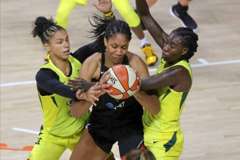 Las Vegas Aces' A'ja Wilson, center, is defended by Seattle Storm's Alysha Clark, left, and Nat ...