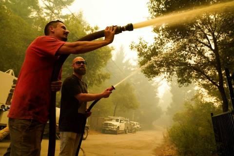 Civilian volunteers Brian Alvarez, left, and Nate Bramwell fight the CZU Lightning Complex Fire ...