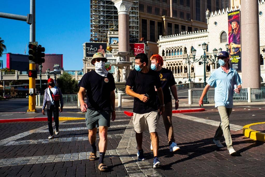 People wearing masks walk along the Las Vegas Strip on Friday, July 17, 2020. (Chase Stevens/La ...