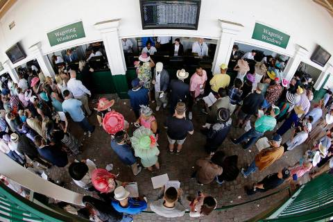 In this May 3, 2014, file photo, taken with a fisheye lens, fans line up to place bets before t ...