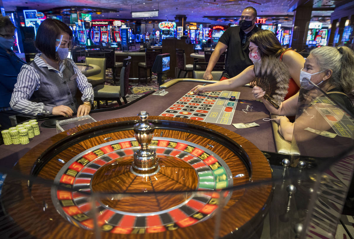 Roulette croupier Umee Mercado, left, looks on as players Ted, Stepheni and Estrella Steele fro ...