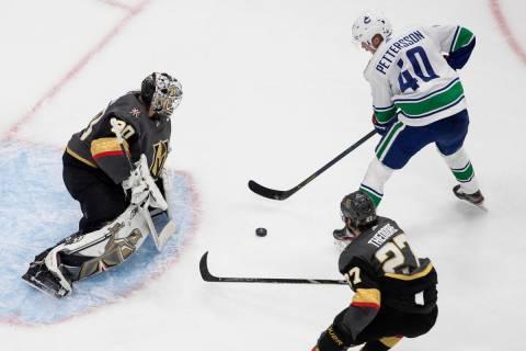 Vegas Golden Knights goalie Robin Lehner (90) stops Vancouver Canucks' Elias Pettersson (40) as ...