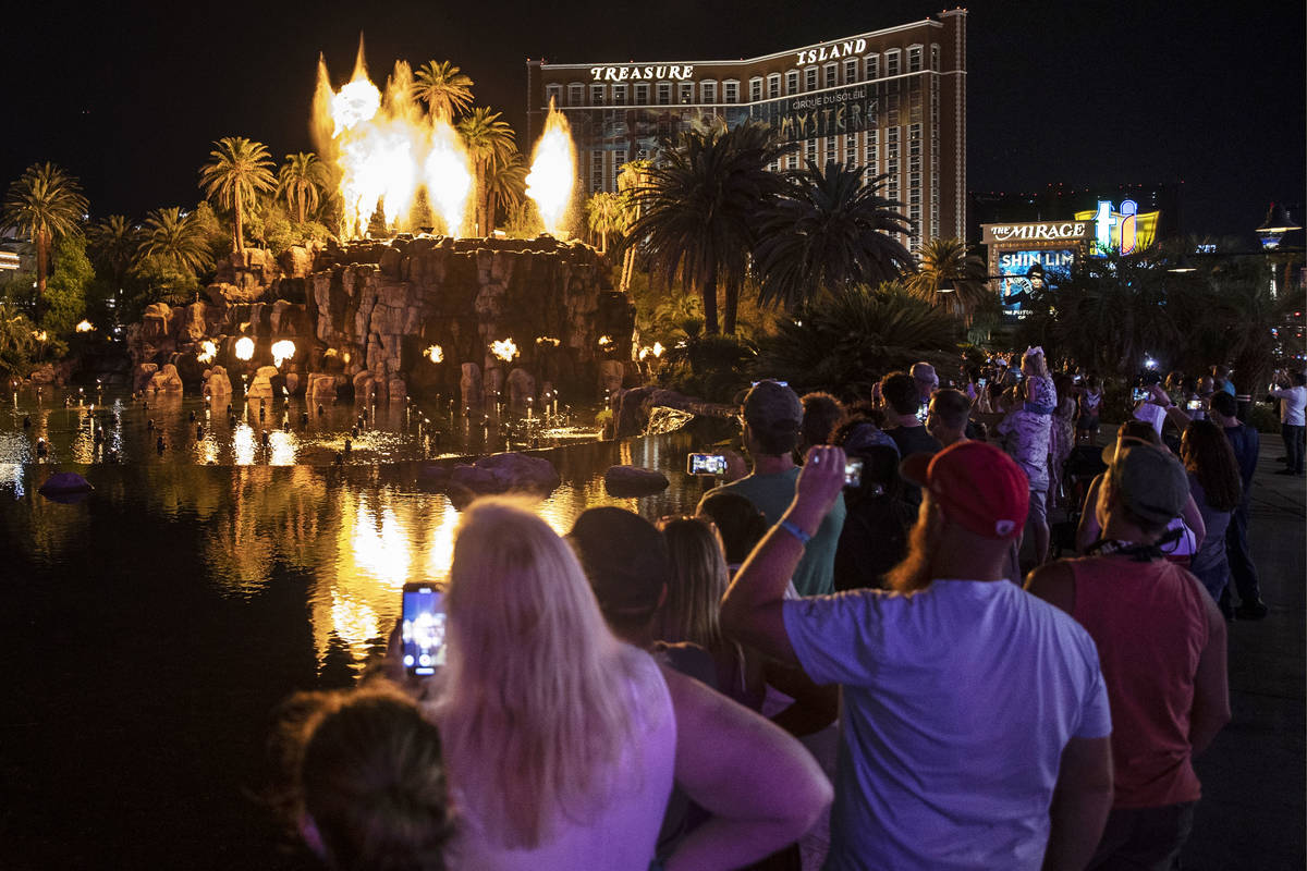 People on the Strip watch the first volcano show since the opening of the The Mirage earlier in ...
