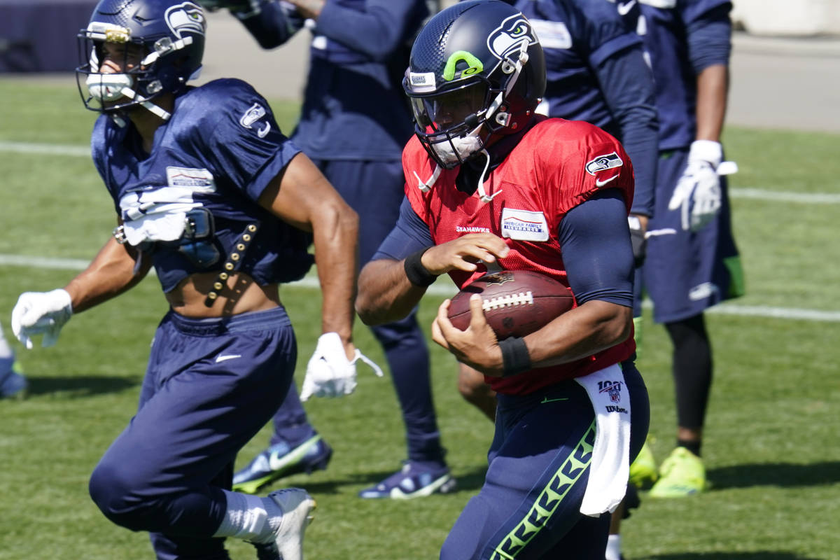 Seattle Seahawks quarterback Russell Wilson runs with a ball Sunday, Aug. 30, 2020, during an N ...