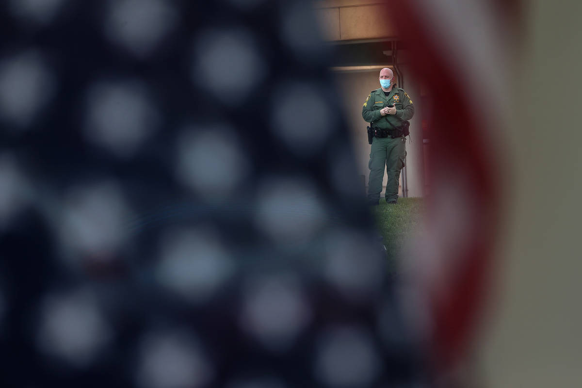 A Las Vegas police officer monitors a No Mask Nevada PAC rally from across the street at Sunset ...