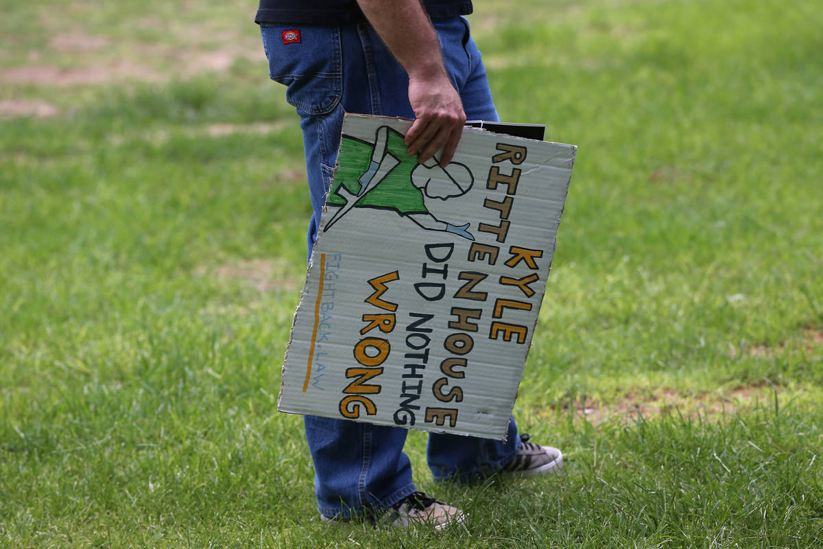 A man participating in a No Mask Nevada PAC rally displays a sign at Sunset Park in Las Vegas, ...