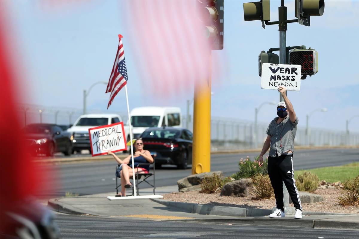 Counter protester Sascha Alexander displays his sign during a No Mask Nevada PAC rally at Sunse ...