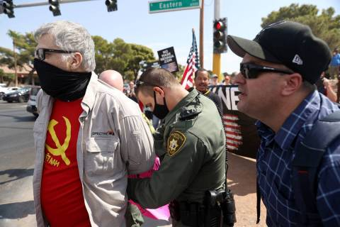A counterprotester is detained by Las Vegas police at a No Mask Nevada PAC rally at Sunset Park ...