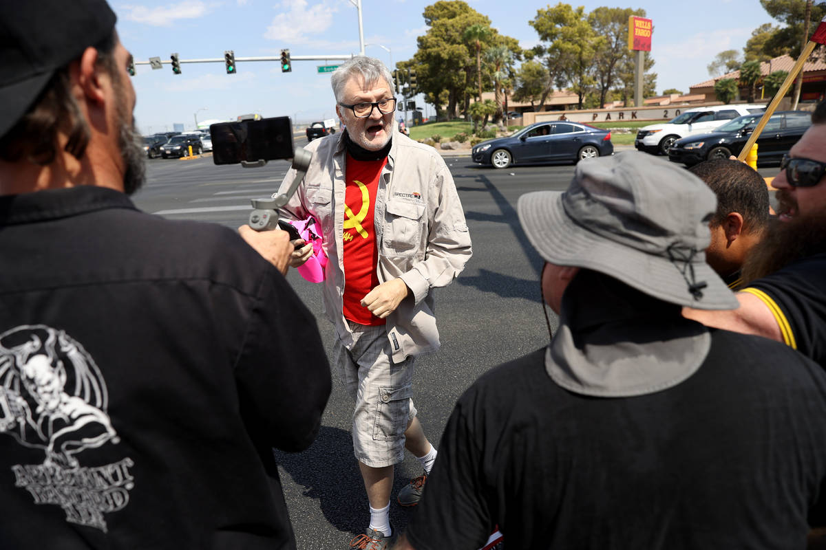 A counterprotester is confronted by people participating in a No Mask Nevada PAC rally at Sunse ...