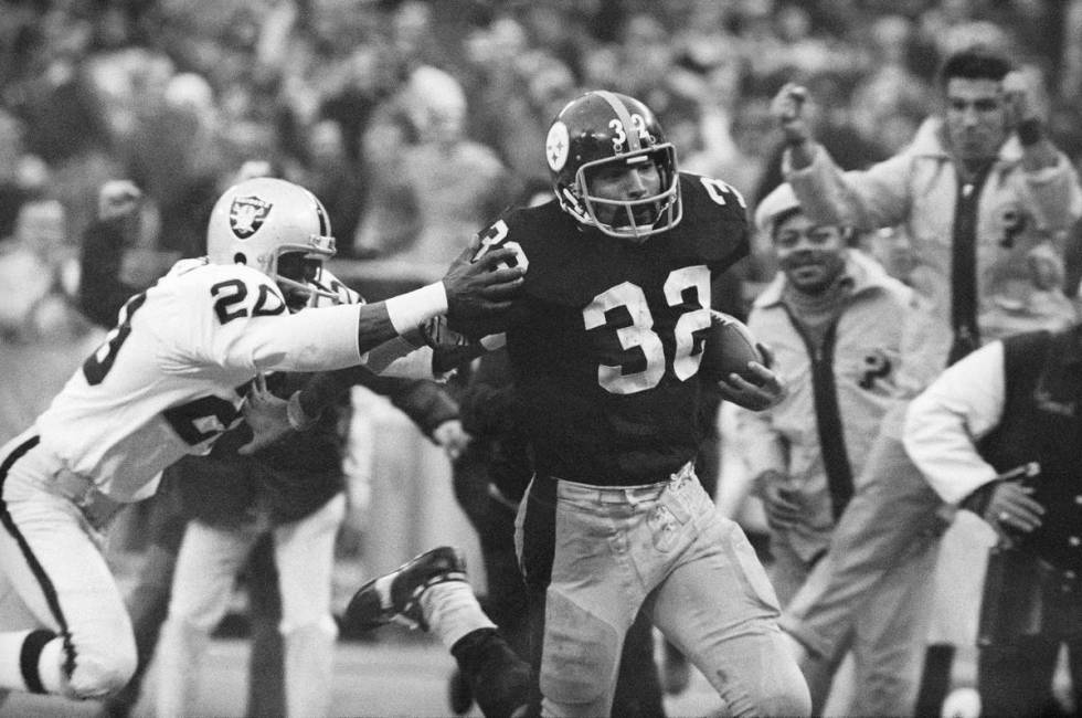 """The Steelers' Franco Harris eludes the Raiders' Jimmy Warren en route to his """"Immaculate ..."""