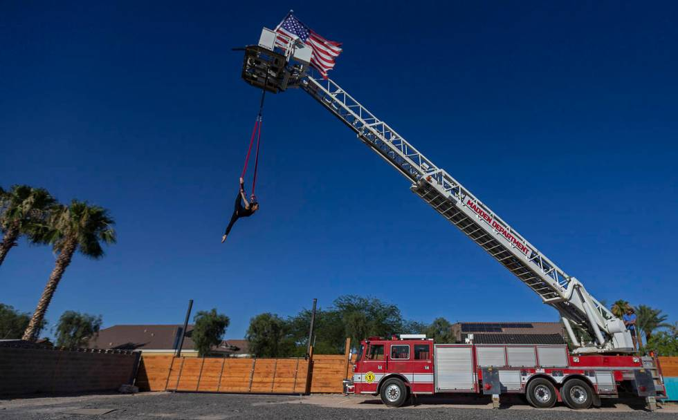 Elema Sanders practices on aerial straps attached to an out-of-service fire truck at the home o ...
