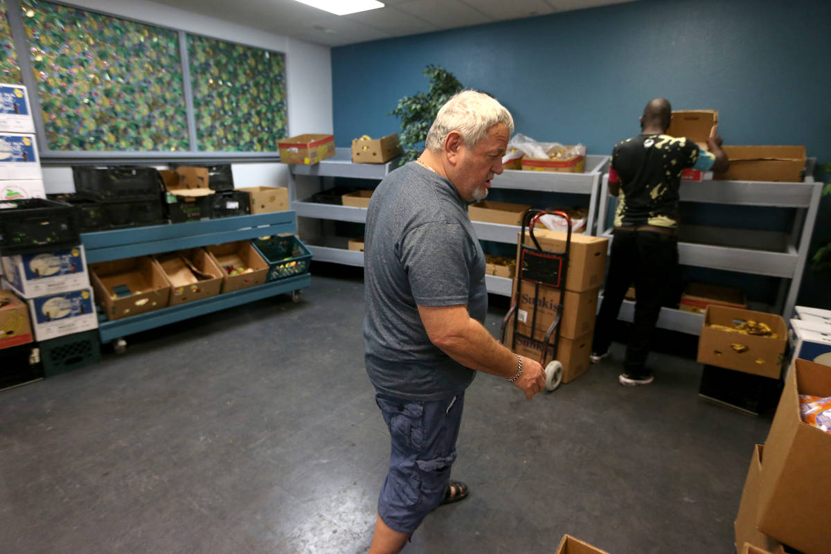 Vic Caruso, director of one food pantry, gives a tour of the City Impact Center food pantry in ...