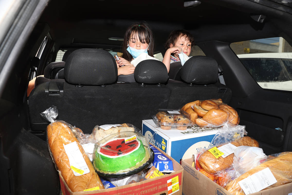 Zamira, 5, and her sister Zeriah Basulto, 5, of Las Vegas, looks at food their family received ...