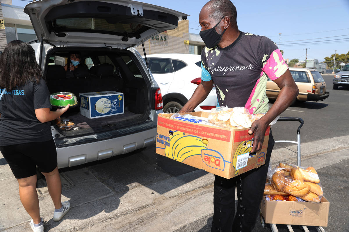Volunteer Gregory Jones, right, assists Wendy Basulto with taking food to her car at the City I ...
