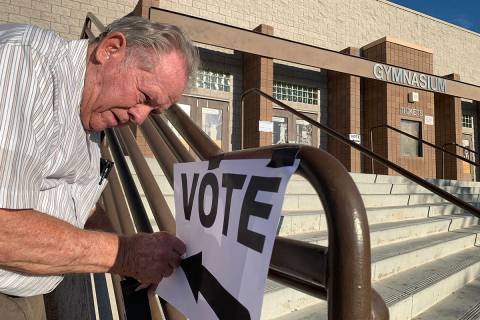 FILE--Poll worker Donald Somerville tapes up a sign for municipal elections at Bonanza High Sch ...