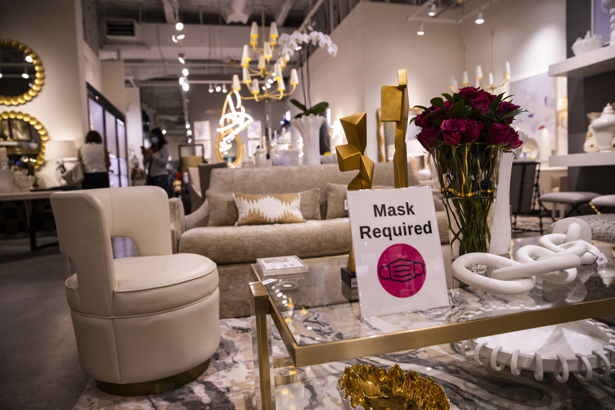 """A sign stating """"mask required"""" is seen at the Global Views showroom at the Summer Las ..."""
