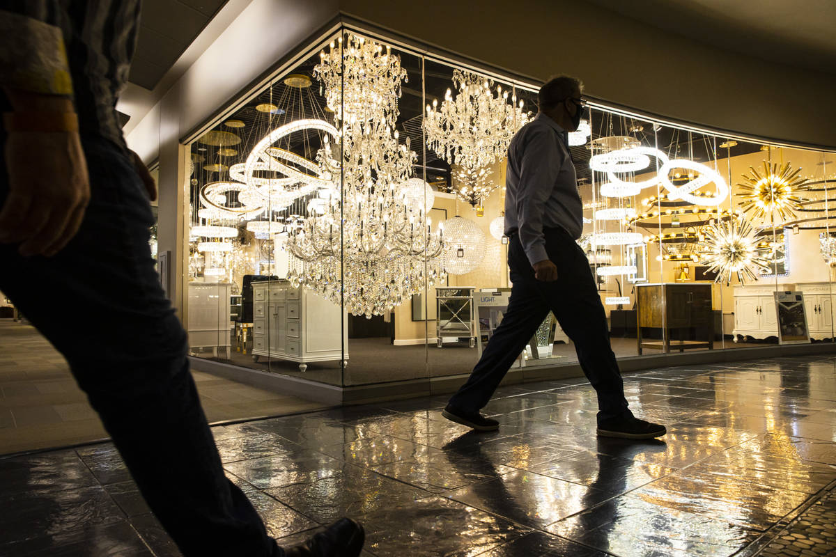 Attendees wearing face masks walk by the Elegant Furniture & Lighting showroom during the S ...