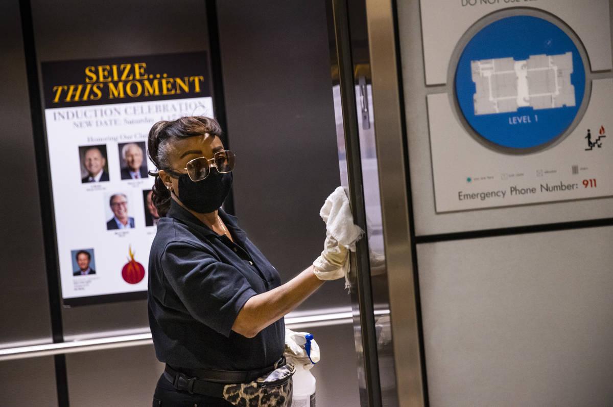 Louvenia Madison sanitizes elevators during the Summer Las Vegas Market at the World Market Cen ...