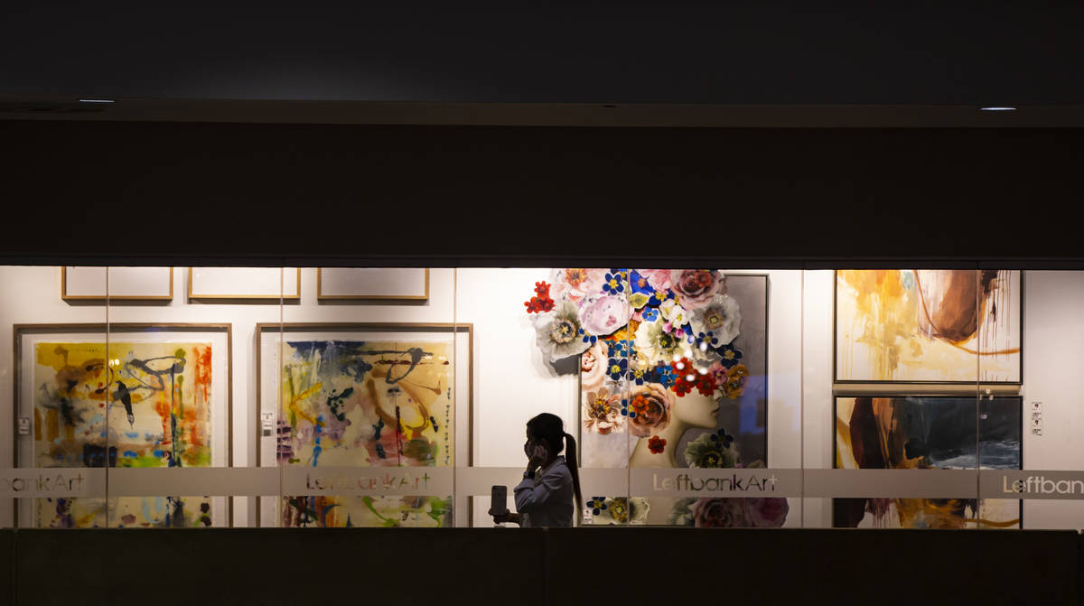A woman adjusts her mask while walking by the Leftbank Art showroom during the Summer Las Vegas ...