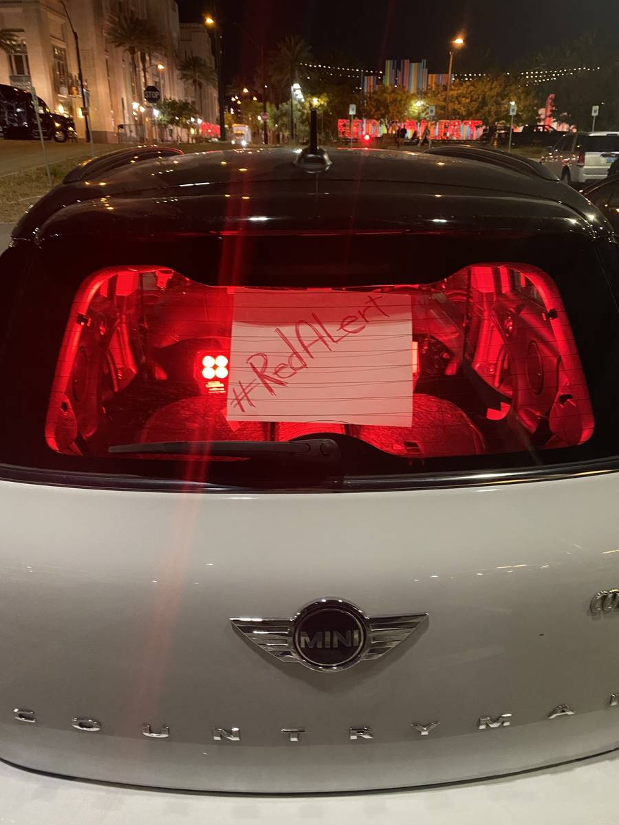A Mini Cooper with its interior lit up in red is shown in the Smith Center parking lot during t ...