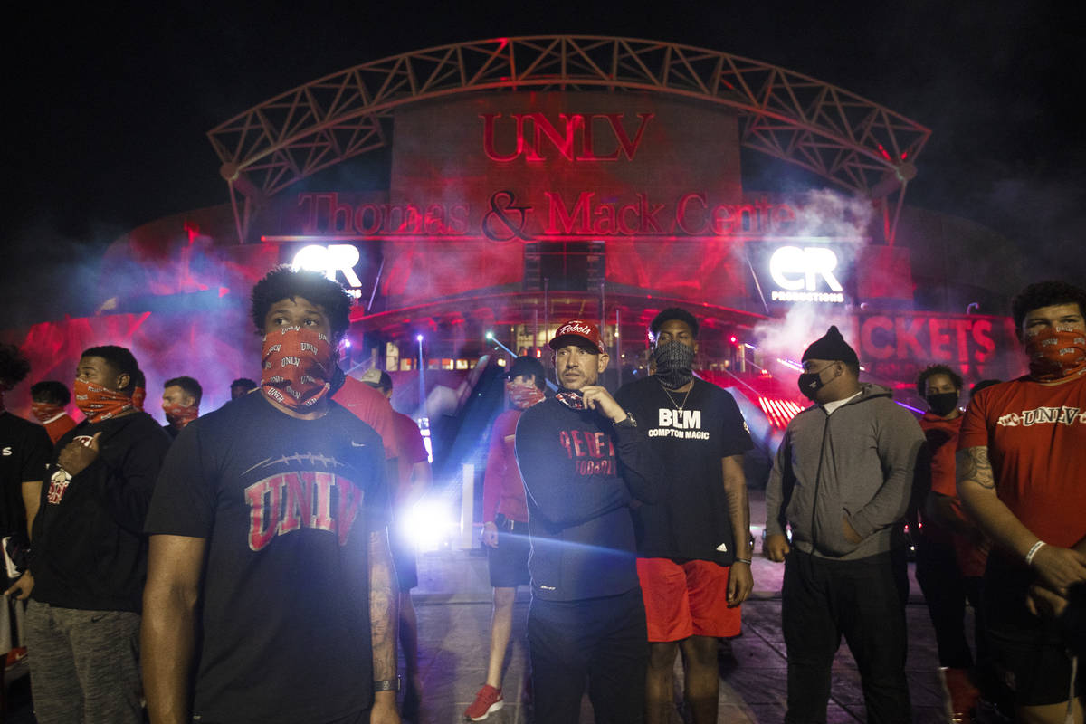 UNLV head football coach Marcus Arroyo, middle, stands in front of a glowing red Thomas and Mac ...