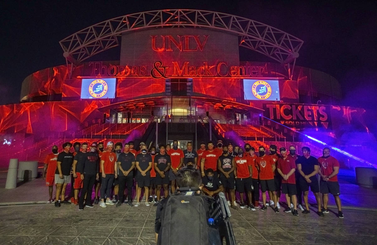 A group of UNLV football players, including head coach Marcus Arroyo, stand in front of a glowi ...