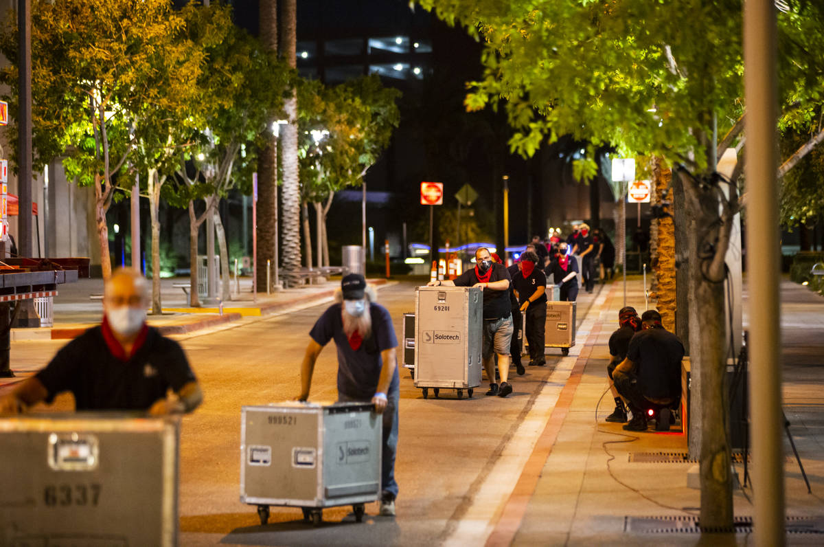 """Entertainment workers push road cases around The Smith Center as it turns red for the """"Red ..."""